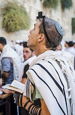 A Jewish man wearing tefillin (phylacteries) and a tallit (prayer shawl)